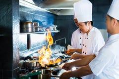 Cozinheiros chefe asiáticos que cozinham no restaurante Imagem de Stock