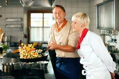 Cozinheiros chefe em um cozimento da cozinha do restaurante ou do hotel Foto de Stock Royalty Free