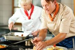 Cozinheiros chefe em um cozimento da cozinha do restaurante ou do hotel Imagens de Stock Royalty Free