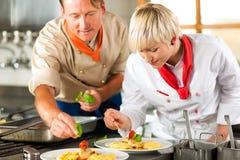 Cozinheiros chefe em um cozimento da cozinha do restaurante ou do hotel fotografia de stock royalty free