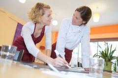 Cozinheiros chefe fêmeas felizes que trabalham junto imagens de stock