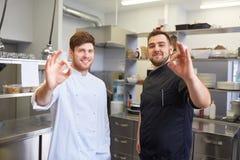 Cozinheiros chefe felizes na cozinha do restaurante que mostra o sinal aprovado Imagem de Stock