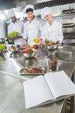 cozinheiros chefe multiculturais na cozinha do restaurante com livro da receita fotografia de stock