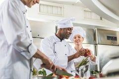 cozinheiros chefe multiculturais que preparam vegetais maduros fotos de stock