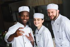 cozinheiros chefe multiculturais que tomam o selfie com smartphone fotografia de stock royalty free