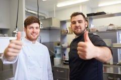Cozinheiros chefe na cozinha do restaurante que mostra os polegares acima Imagem de Stock Royalty Free