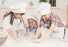Cozinheiros chefe pequenos felizes que preparam a massa na cozinha Fotos de Stock Royalty Free