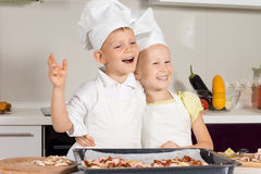 Cozinheiros chefe pequenos muito felizes após ter cozido a pizza Foto de Stock