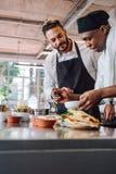 Cozinheiros chefe que cozinham o prato novo do alimento na cozinha Imagens de Stock