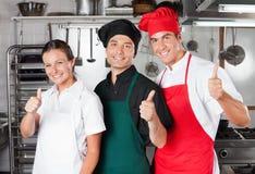 Cozinheiros chefe que dão os polegares acima fotografia de stock royalty free