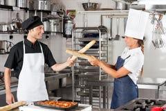 Cozinheiros chefe que lutam com Loafs do pão Fotos de Stock
