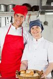 Cozinheiros chefe que mantêm a cesta completa dos pães Fotos de Stock Royalty Free