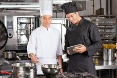 Cozinheiros chefe que preparam o alimento na cozinha Fotografia de Stock