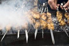 Cozinheiros da carne em carvões quentes no fumo Piquenique na natureza foto de stock