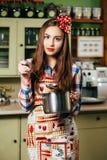 Cozinheiros da jovem mulher na cozinha imagem de stock