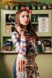 Cozinheiros da jovem mulher na cozinha fotografia de stock
