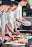 Cozinheiros do homem que preparam o sushi Fotos de Stock Royalty Free