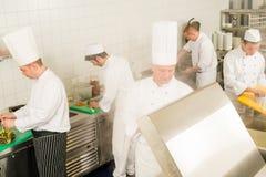Cozinheiros e cozinheiro chefe ocupados da equipe da cozinha profissional Imagem de Stock
