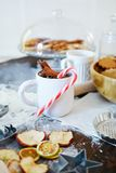 Cozy and appetizing table with a Cup of cinnamon and festive candy. A Cup of cinnamon and a festive candy decorate the table on which to lie cookies and dried stock photo