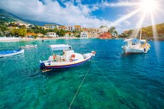 Cozy Assos village in Kefalonia. Colorful boats in azure bay under morning sunlight. Sommer vacation in Greece.  stock image