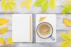 Cozy autumn breakfast with morning cup of coffee and open notebook on rustic wooden table top view. Fall bucket list. Flat lay. Stock Photography