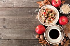 Cozy autumn breakfast scene on rustic wood. Table with oatmeal, coffee, fruit and nuts Royalty Free Stock Photos
