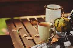 Cozy autumn morning at country house, cup of tea and warm blanket on wooden table Royalty Free Stock Photos