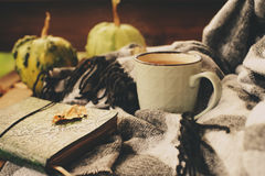 Cozy autumn morning at country house, cup of tea and warm blanket on wooden table. Still life details Stock Photo