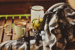 Cozy autumn morning at country house, cup of tea and warm blanket on wooden table. Still life details Royalty Free Stock Images