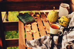 Cozy autumn morning at country house, cup of tea and warm blanket on wooden table. Still life details Royalty Free Stock Image