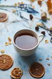 Cozy autumn morning with cup of tea, decorative lavender, dried oranges and autumn leaves on light blue background, teatime, hugge. Cozy autumn morning with cup stock images