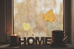 Cozy autumn morning at home. Hot tea and candle on window in rainy cold day. Spending holidays at home stock photography