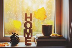 Cozy autumn morning at home. Hot tea and candle on window in rainy cold day. Spending holidays at home stock photo
