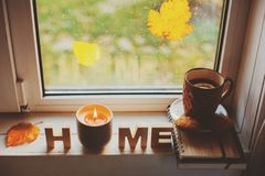 Cozy autumn morning at home. Hot tea and candle on window in rainy cold day. Spending holidays at home royalty free stock photography