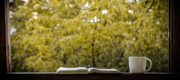 Cozy autumn still life: cup of hot coffee and opened book on vintage windowsill and rain outside. Autumn. Apartment. Rain.  royalty free stock photos