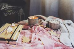 cozy autumn or winter morning at home. Still life details with cup of hot cocoa, candle, sketch book with herbarium and warm sweat royalty free stock images