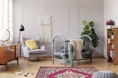 Comfortable armchair and grey wooden crib, real photo. Cozy baby room with comfortable armchair with yellow pillow and grey wooden crib, real photo stock photo
