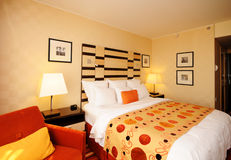 Cozy Bed. Spacious and nicely deocrated room. Orange Theme with King Bed stock photography