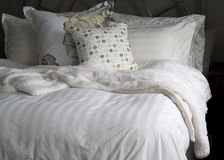 Cozy Bed Linens. A restful night's sleep awaits in a comfy bed with a down duvet and fluffy pillows Stock Photos