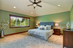 Cozy bedroom with blue bed, buttons headboard and green walls Stock Photos