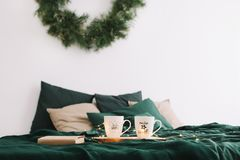 Cozy bedroom with coffee mugs and book in bed. Christmas still life. Holidays, Christmas and New Year concept. Cozy bedroom with coffee mugs and book in bed stock photography