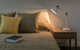 Cozy bedroom interior with book and reading lamp on bedside tabl Stock Images