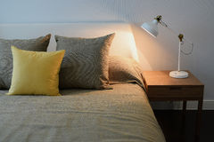 Cozy bedroom interior with pillows and reading lamp Stock Photography