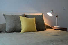 Cozy bedroom interior with pillows and reading lamp Stock Image