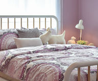 Cozy bedroom interior with pillows and reading lamp on bedside table Royalty Free Stock Image