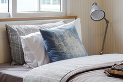 Cozy bedroom interior with pillows and reading lamp on bedside table at home Stock Photos