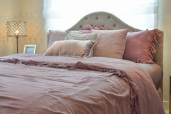 Cozy bedroom interior with pillows and reading lamp Royalty Free Stock Photos