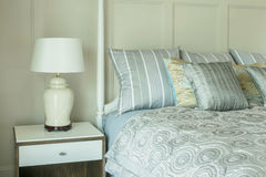 Cozy bedroom interior with pillows and reading lamp on table Royalty Free Stock Photos