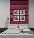 Cozy bedroom interior with pink/red colored wall Stock Images