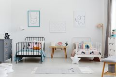 Cozy bedroom interior for siblings. Two beds, one white, one black with patterned bedding and posters of a rabbit and elephant on. The wall. Real photo stock image